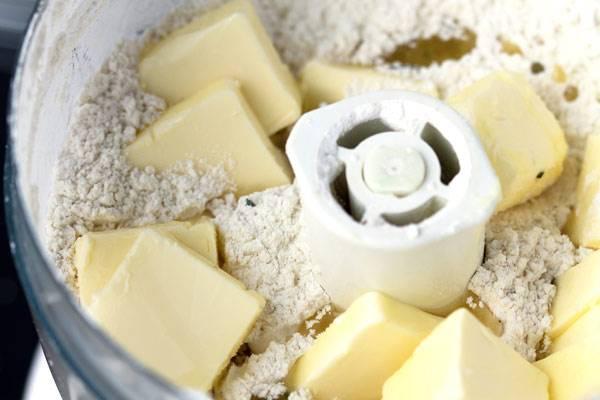 1. Чтобы ускорить процесс и замесить однородное тесто, предлагаю использовать кухонный комбайн. В него всыпьте сахар, добавьте просеянную муку, щепотку соли и холодное сливочное масло. Количество сахара варьируйте по вкусу.