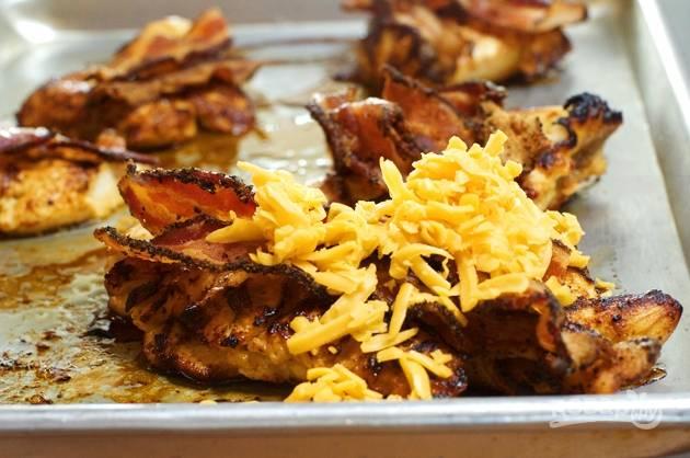 5. Обжаренные филе выложите на противень, сверху положите пару ломтиков бекона и присыпьте тертым сыром. Отправляйте противень в заранее разогретую духовку на 5 минут. Как только сыр расплавится, доставайте и подавайте к столу!