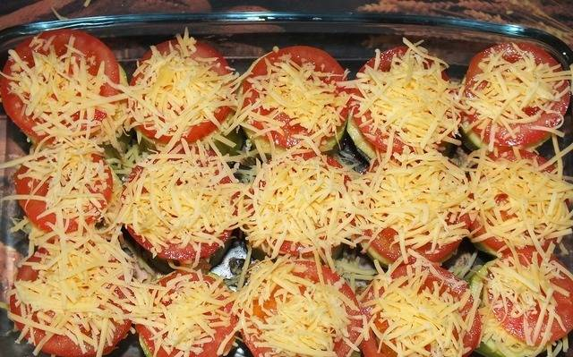 Помидоры нарезать кружочками, сыр натереть на терке. Закрыть кабачки кружочками помидор и посыпать тертым сыром.