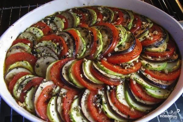 Раздавите или мелко порежьте чеснок и смешайте его с оливковым маслом чтобы получить соус для смазывания блюда. На дно формы выложите готовый соус из томатов, лука и перца, разравняйте его. Просушите баклажан и выложите нарезанные кольцами помидоры, кабачок и баклажан красивой спиралью, чередуя эти овощи. Сверху помажьте рататуй оливковым маслом с чесноком, накройте форму фольгой и отправьте в духовку на среднюю температуру на полтора часа. Затем снимите фольгу и запеките блюдо ещё 20 минут. Теперь оно готово.