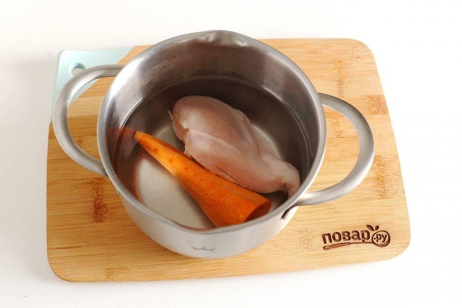 Морковь очистите и выложите в кастрюлю. Добавьте куриное филе, налейте воду и отварите до готовности.
