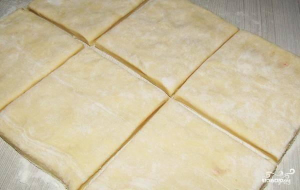 Тесто разморозьте. Присыпьте поверхность, на которой будете готовить, мукой. Растяните на ней тесто, нарежьте его одинакового размера квадратами.