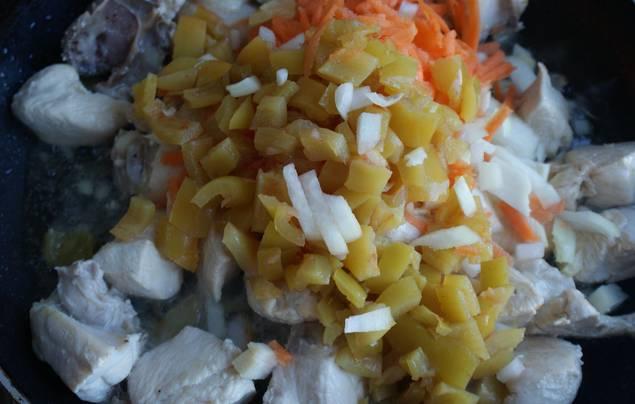 Добавляем мелко порезанные лук и перец, а также тертую морковь. Готовим еще 5-6 минут.