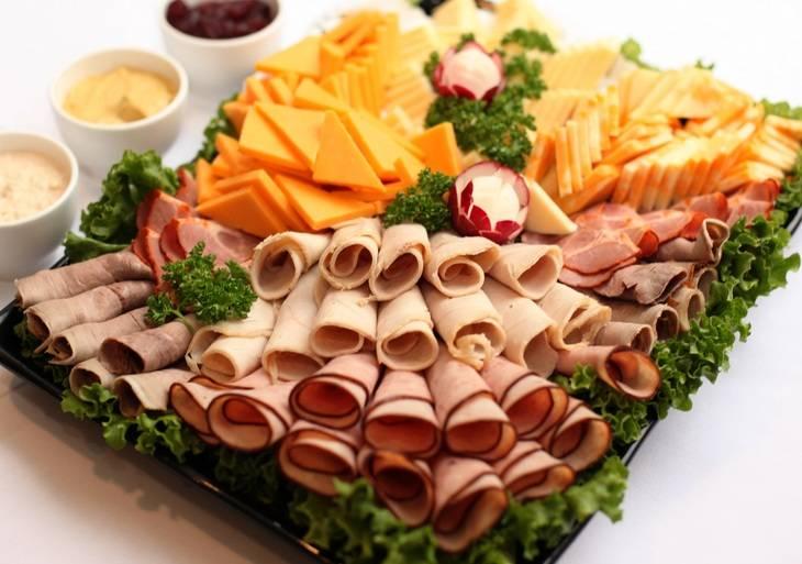 """Существет множестов вариантов красивой праздничной нарезки колбасы и сыра. Одним из самых популярных вариантов нарезки считаются """"Рулетики"""". В таком варианте колбаса и остальное мясо нарезается стандартными ломтиками. Каждый ломтик скручиваем в рулетик. Сыр нарезаем маленькими треугольничками. Красиво укладываем все на блюдо, украсив по бокам зеленью."""