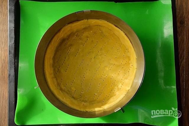 Тесто разделите на две части: 2/3 и 1/3. Большую часть тонко раскатайте и распределите руками по форме для запекания (у меня разъемное кольцо, d - 22 см), сформируйте бортики. Наколите тесто вилкой, поставьте в разогретую до 200 °С духовку на 15 минут.