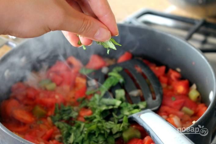 Посолите и поперчите соус по вкусу. Добавьте томатную пасту, орегано и порезанный базилик. Тушите около часа, помешивая каждые 10 минут. За 15 минут забросьте в соус нарезанные цукини и потушите.