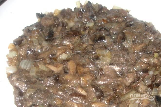 Лук нарежьте кубиками. Обжарьте 5 минут в масле до мягкости. Потом добавьте мелко нарезанные грибы. Жарьте ингредиенты вместе в течение 10-15 минут.