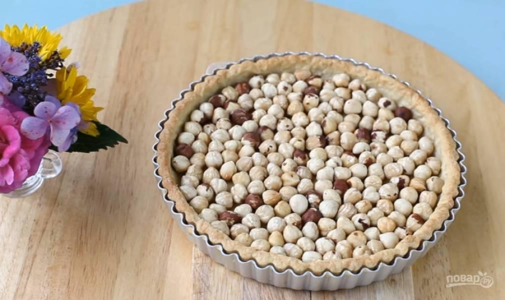 7. Поджарьте в духовке орехи, очистите их от шелухи. Равномерно насыпьте орехи в форму.