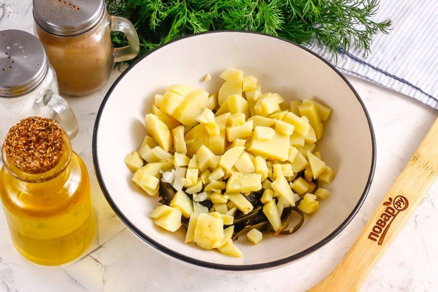 Очистите от кожуры отварной картофель и промойте, нарежьте мелкими или средними кубиками, добавляя в емкость.
