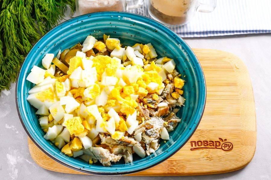 Очистите от скорлупы отварные куриные яйца, промойте их в воде и нарежьте мелким кубиком. Добавьте нарезку в емкость.