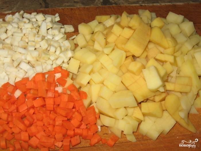 Картофель очистите и нарежьте кубиками. Чем мельче вы его нарежете, тем быстрее он сварится. Также очистите морковочку, сельдерей и корень петрушки, которые следует нашинковать кубиками.