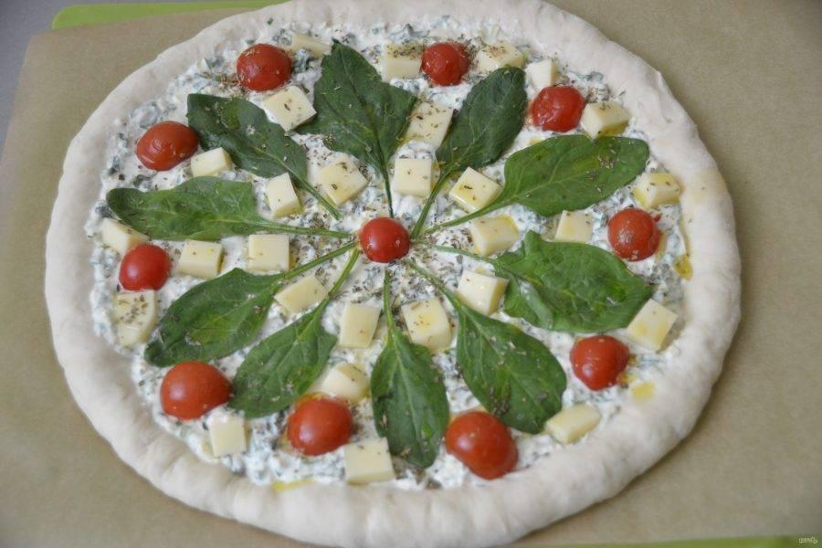 Моцареллу порежьте кубиком и уложите в промежутках между шпинатом и черри. Сбрызните перед выпечкой пиццу немного оливковым маслом и присыпьте сухим орегано или базиликом.
