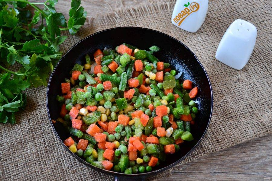 Добавьте в сковороду замороженные овощи и слегка обжарьте.