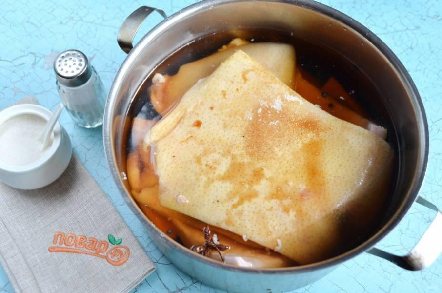2. Сложите шкуру в кастрюлю, залейте чистой холодной водой, положите сразу все специи и соевый соус. Солите по вкусу, рассол должен быть чуточку пересолен. Варите при слабом кипении около часа.