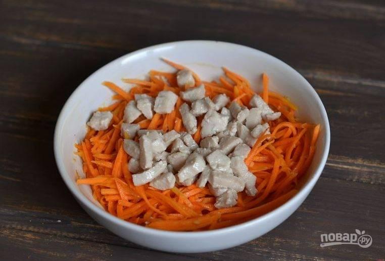 Достаньте из холодильника маринованную морковь, слейте из миски лишнюю жидкость, которую выделит морковь. Добавьте к ней обжаренную на растительном масле курочку.