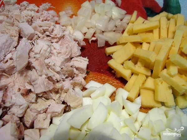 Куриную грудку порежьте тонкой соломкой, также можно просто разделить её на волокна. Сыр, томат и лук порежьте мелкими кусочками. Вареное яйцо тоже мелко порежьте.