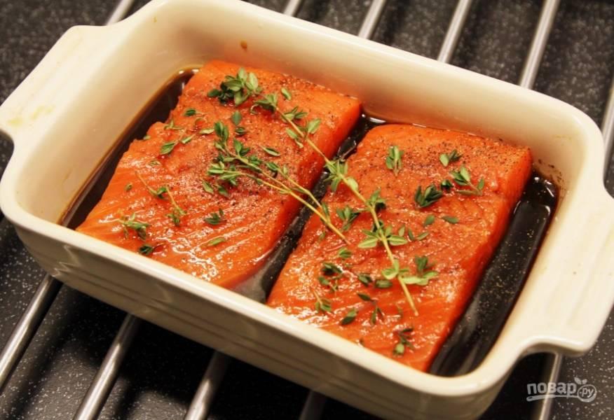 """Рыбку разрежьте на 2 куска. Форму для выпечки смажьте маслом. Уложите в неё лосось и влейте соус """"Терияки"""". Поперчите филе, а сверху украсьте его тимьяном."""