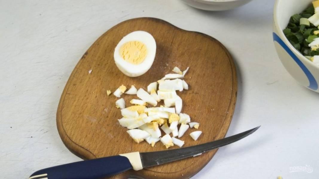 Яйца отварите вкрутую. Затем остудите их, почистите, нарежьте и соедините с луком.
