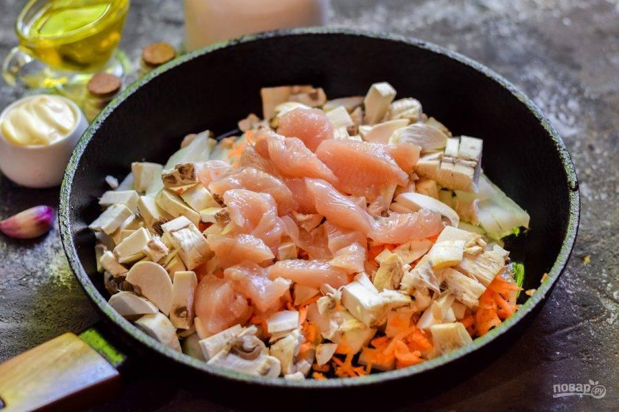 Ополосните и нарежьте кубиками куриное филе, добавьте в сковороду.