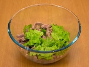 Выкладываем в салатницу мясо, перемешиваем его с листьями салата (порвать руками).