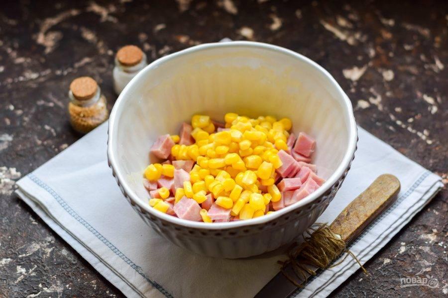 Переложите ветчину в салатник. Добавьте консервированную кукурузу.