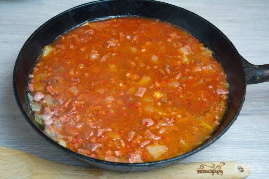Залейте копчености томатным соком и добавьте томатной пасты. От томатной пасты цвет готовой солянки будет ярче и насыщеннее. Кроме того, солянка будет гуще.