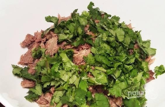 Перекладываем мясо в миску. Туда же отправляем мелко нарезанную оставшуюся кинзу.