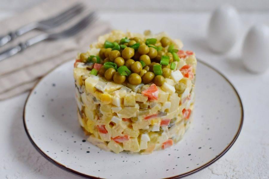 Салат выложите на тарелку для подачи с помощью формовочного кольца, украсьте свежим зеленым луком и консервированным горошком.