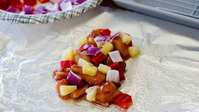 Лук и перец мелко порежьте, ананас обсушите. Выложите курицу, распределив на 4 кусочка фольги, добавьте ананас, лук, перец.