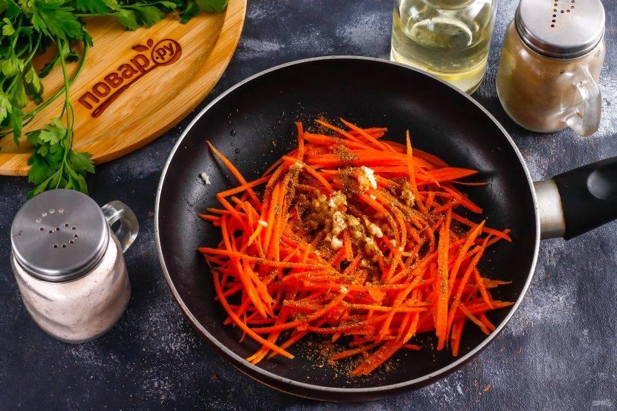 Всыпьте приправу для моркови по-корейски, щепотку соли и поместите емкость на плиту. Обжарьте примерно 1-2 минуты и выключите нагрев. Дайте моркови слегка остыть.