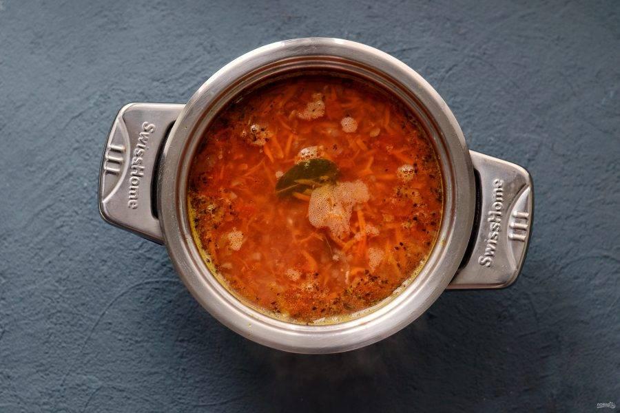 Добавьте томатную пасту, перец и соль. Продолжайте варить суп на медленном огне ещё 20-30 минут.