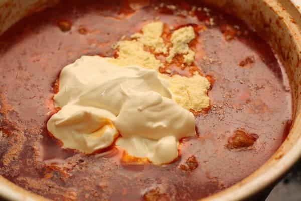 Когда мясо стало мягким, добавляем к нему сметану и кукурузную муку.
