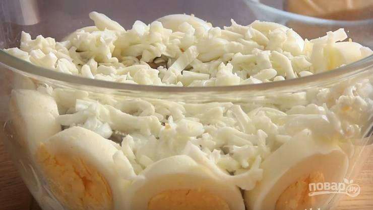 4. В центр выложите жареные грибы с луком и накройте их натертым на крупной терке яичным белком. Затем сделайте сеточку из майонеза.