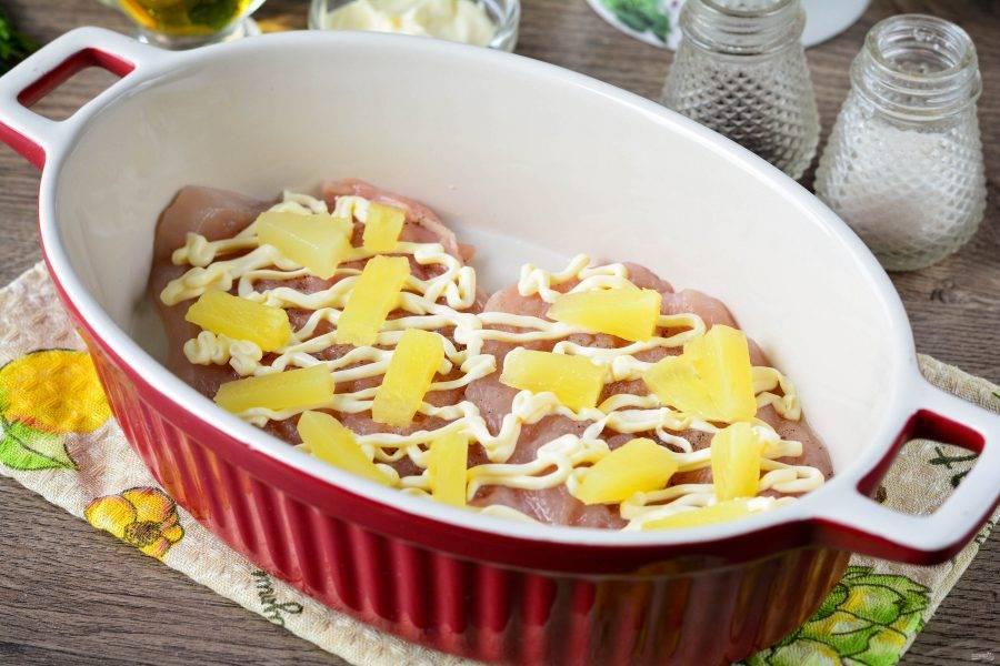 Выложите кусочки ананасов на куриные отбивные.