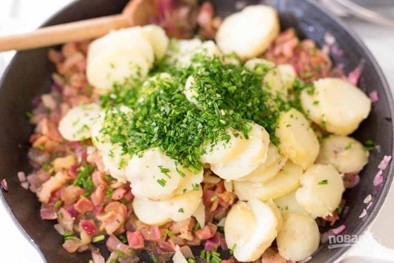 8. Промойте и измельчите зеленый лук, петрушку. Положите картофель в сковороду с беконом и посыпьте сверху зеленью.