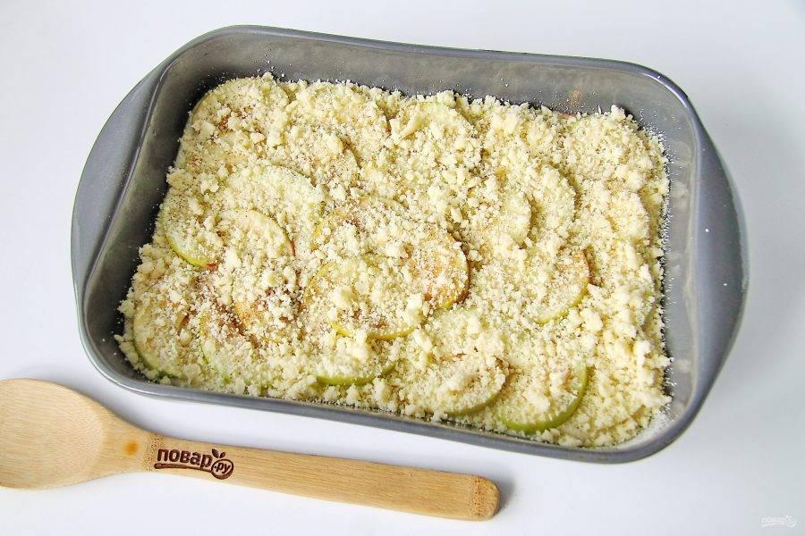 На яблоки вылейте оставшееся тесто и сверху выложите вторую половину нарезанных яблок. Посыпьте яблоки корицей и подготовленной крошкой (штрейзелем). Выпекайте в духовке при температуре 180 градусов около часа.