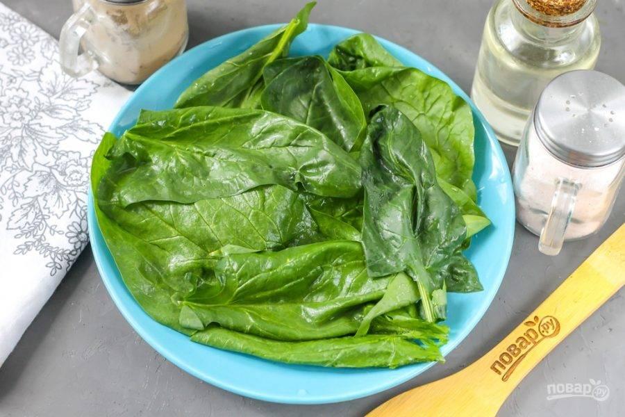 Срежьте стебли с пучка шпината, разберите его на листья и промойте каждый из них, затем обсушите с помощью бумажных полотенец. Выложите свежую зелень на тарелку. Если вы не любите свежий шпинат, то зелень можно обдать кипятком, поместив в дуршлаг, а затем стряхнуть лишнюю влагу и выложить на тарелку.