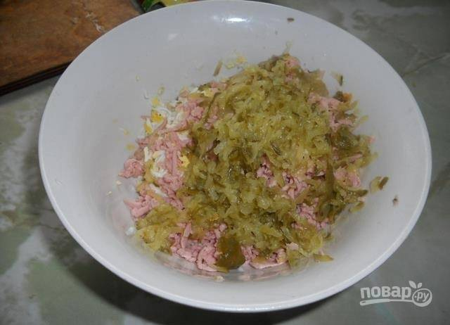 2. Натрите на крупной терке колбасу и огурцы. Огурцы перед смешиванием с другими ингредиентами нужно отжать от лишней жидкости.