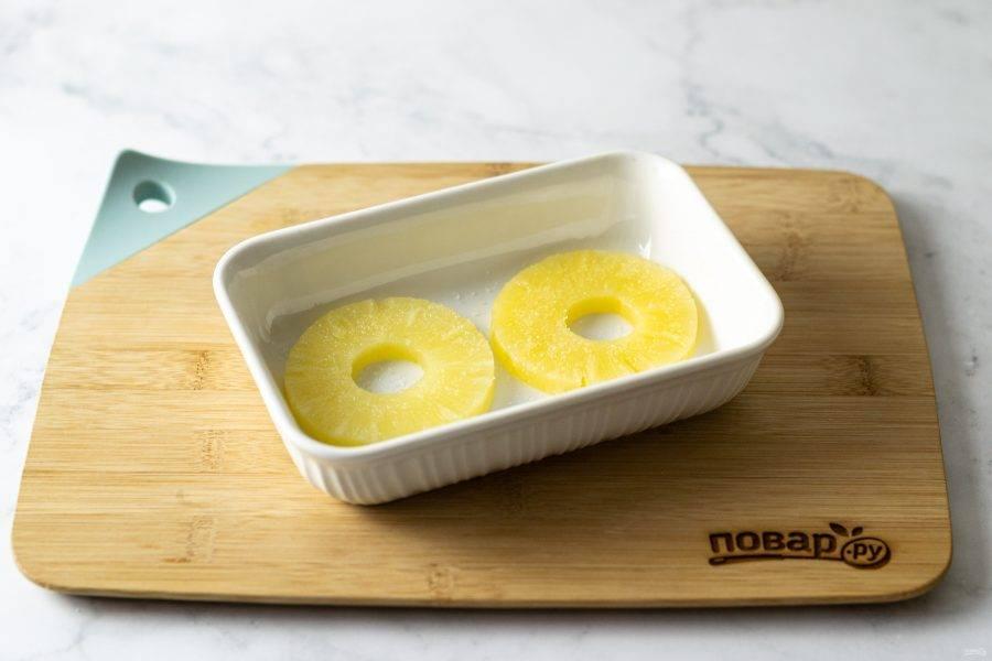Выложите кружочки ананасов в форму для выпечки. Разогрейте духовку до 200 градусов. Присыпьте ананасы сахаром и запекайте до образования карамельной корочки. Примерно 20-25 минут.