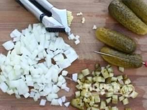 Чеснок и лук почистите и мелко нашинкуйте. Соленый огурец порежьте мелким кубиком.