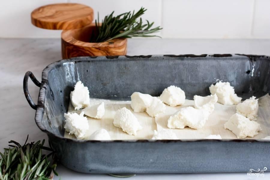 Теперь займёмся соусом бешамель. Растопите в небольшой кастрюле сливочное масло. Добавьте к нему муки. Перемешайте. Мука станет золотистой. Затем налейте молока, добавьте немного розмарина и доведите до кипения. Постоянно помешивайте, соус должен немного загустеть. Добавьте моцареллы, мускатный орех и белый перец. Постоянно помешивайте соус бешамель. Моцарелла полностью расплавится, размягчится и можете снимать с огня. Приготовьте форму для выпекания, смажьте её оливковым маслом и уложите первый слой листов для лазаньи. На них выложите кусочки сыра рикотта.