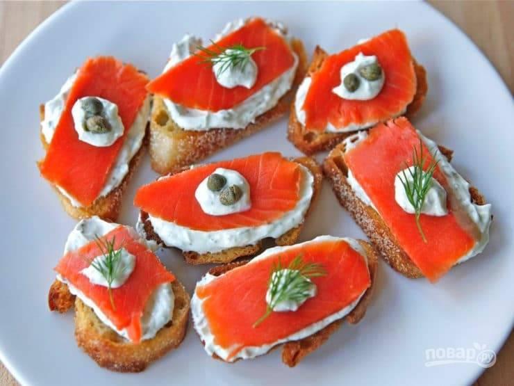 Багет смажьте сливочной смесью. Выложите рыбу. Украсьте канапе каперсами, укропом и намазкой. Приятного аппетита!