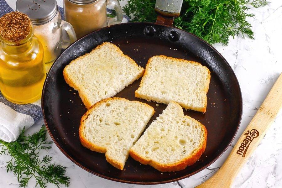 Ломтики хлеба разрежьте пополам диагонально, вертикально или горизонтально — по желанию. Смажьте их растительным маслом и поджарьте на сухой сковороде с обеих сторон до румяности. Затем выложите на тарелку и дайте остыть в течение 5 минут, чтобы они стали хрустящими.