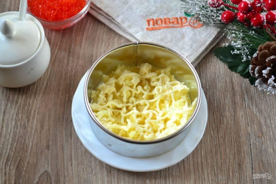На плоскую тарелку поставьте сервировочное кольцо. На дно положите натертый на крупной терке картофель. Сверху покройте майонезной сеточкой.