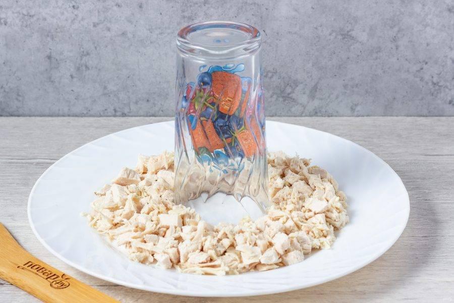 На плоскую тарелку в середину поставьте стакан. Салат будем выкладывать в виде кольца вокруг стакана. Первый слой - нарезанное кубиками куриное филе и майонез.