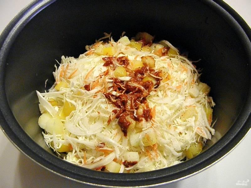 """На дно мультиварки налейте растительное масло. Уложите в кастрюлю капусту, кабачки, лук, морковь, томатную пасту, соль, перец и немного воды (примерно 100 мл.). Если используете томатный сок вместо пасты, воду добавлять не нужно. Перемешайте все. Установите кастрюлю в мультиварку, включите режим """"Суп"""" или """"Каша"""" и тушите 45 минут."""