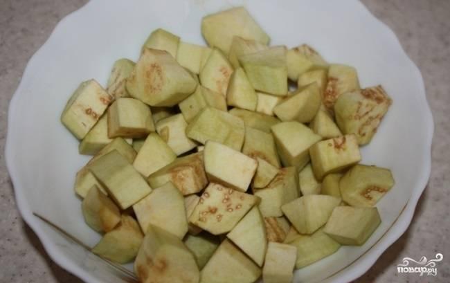 Баклажаны помойте, почистите, нарежьте кубиками. Залейте их холодной водой с солью на 10 минут, чтобы ушла горечь.