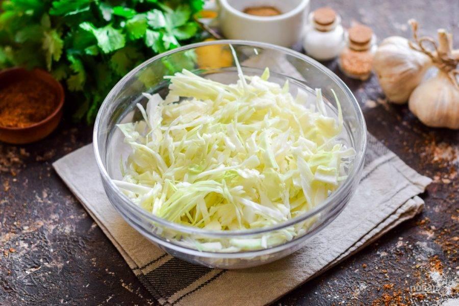 Капусту нашинкуйте тонкой соломкой, несколько верхних листьев капусты отложите.