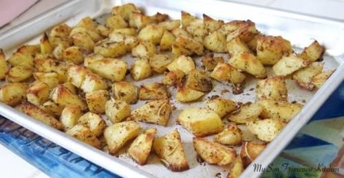 Расстилаем на противне бумагу для запекания и раскладываем по ней картофель. Запекаем картошку в духовке в течение часа при температуре 200 градусов.