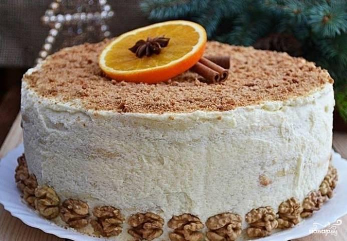 Теперь соберите торт. Выкладывайте коржи друг на друга, смазывая их кремом. Часть грецких орехов измельчите, украсьте ими выпечку. Также красиво уложите дольки апельсина, целые орехи и корицу. Приятной дегустации!